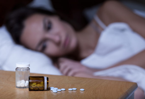 Woman lying in bed, taking sleeping pills