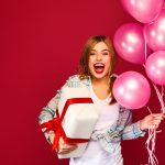 Excited young girl in hipster clothes. Woman model celebrating and holding box with gift present and pink air balloons on red background. St. Women's Day, Happy New Year, birthday holiday party
